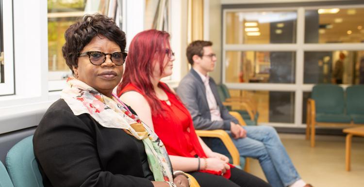 three people sat down in waiting room