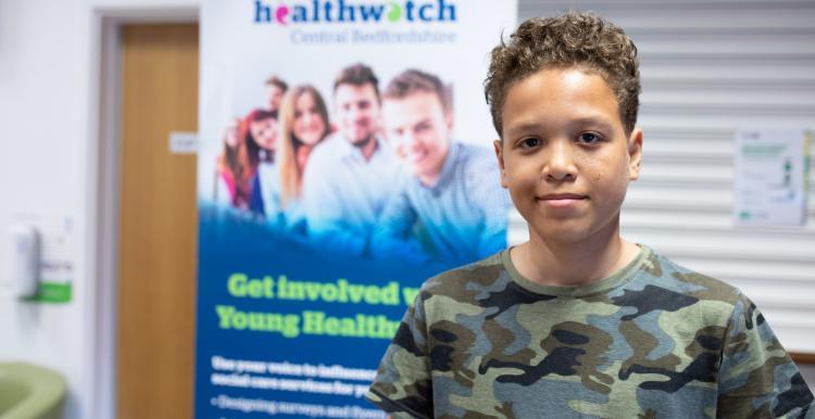 Young male volunteer standing in front of Healthwatch branding