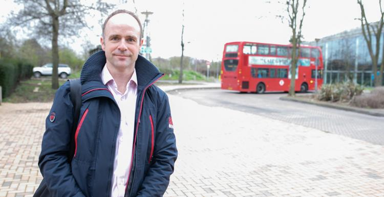 Man stood outside near a roundabout and in front of a bus