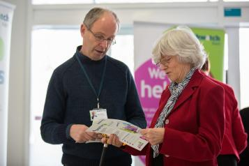 man and woman looking at healthwatch leaflet