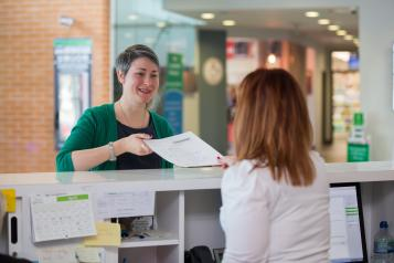 woman handing form to receptionist