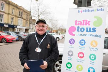 Man standing infront of a Healthwatch Talk to Us sign at a community event