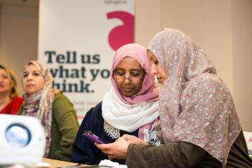 two women speaking at hw meeting