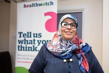 Volunteer standing in front of a Healthwatch banner
