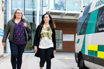 Two women walking next to an ambulance